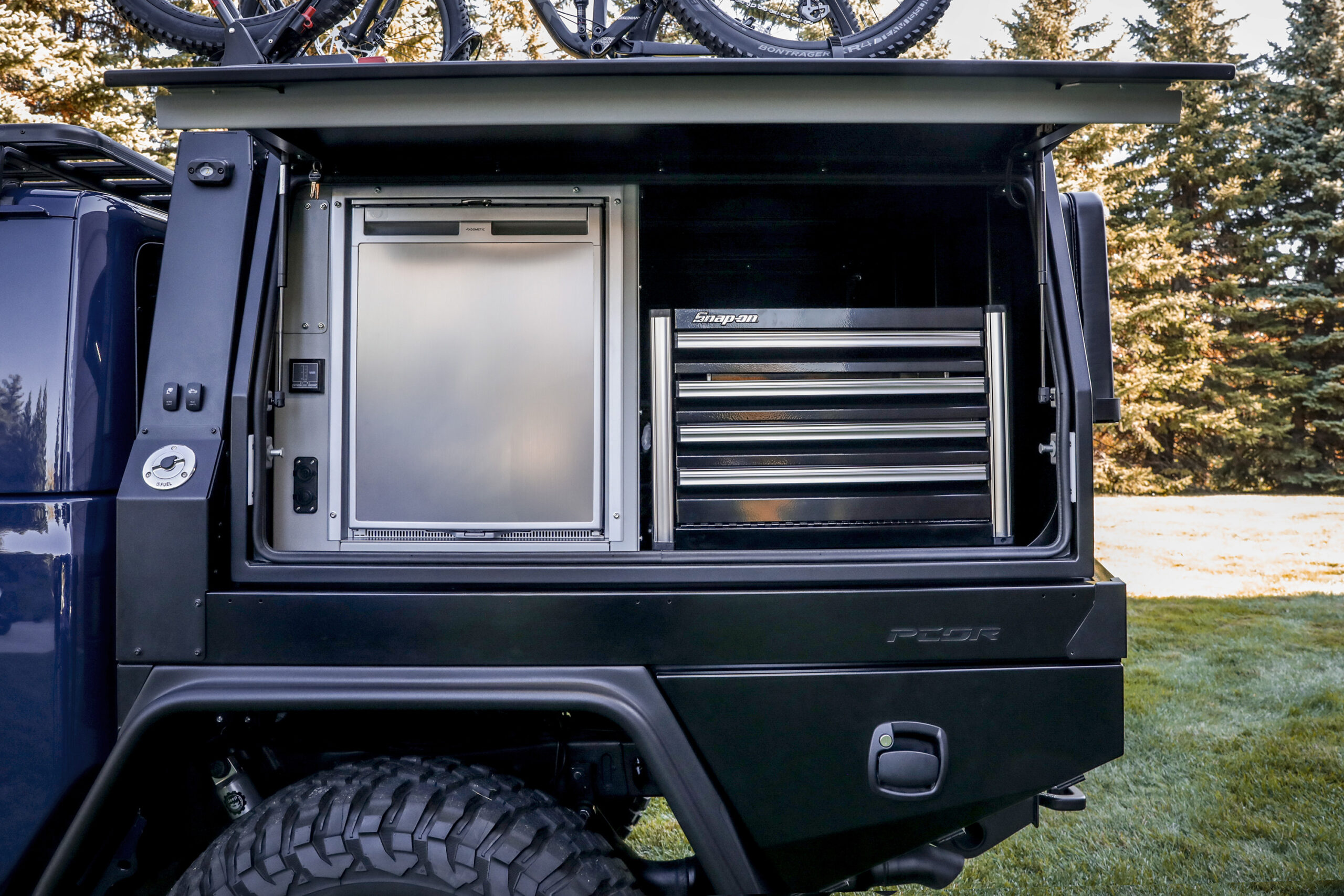 On the driver's-side of the PCOR storage system of the Jeep To